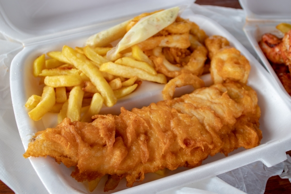 White box with a battered fish and some chips