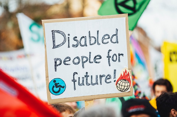 A placard with the words Disabled people for future printed on and a wheelchair symbol amongst a sea of other banners