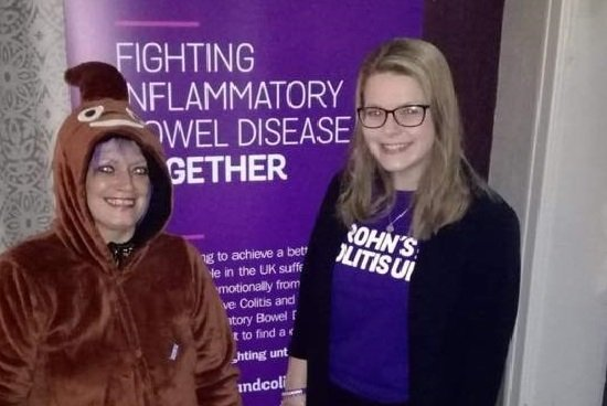 two women one is dressed in a poo emoji onesie and one in a purple crohns and colitis uk tshirt