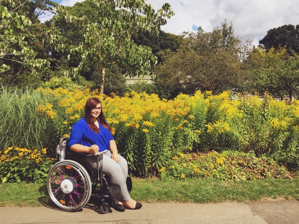 Holly sat in her wheelchair with colourful flowers behind her