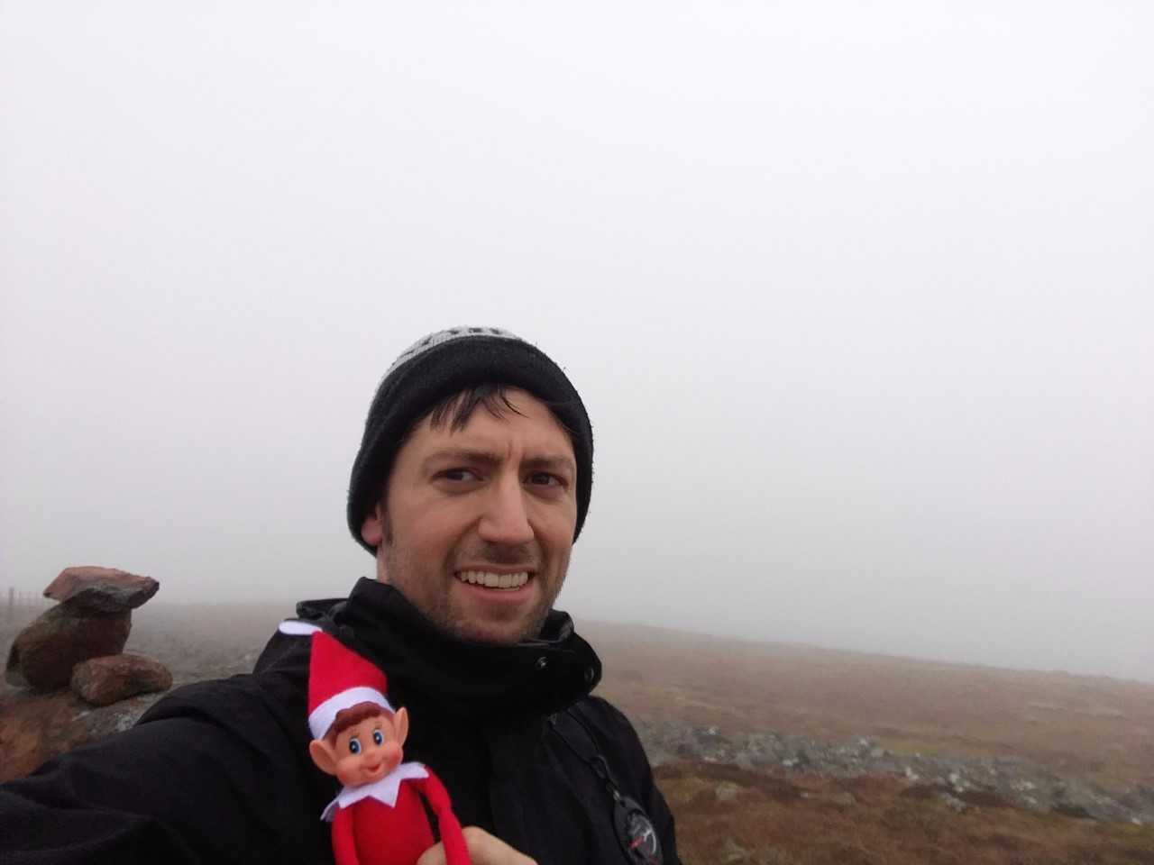 headshot of man holding little red elf with mountains in the background