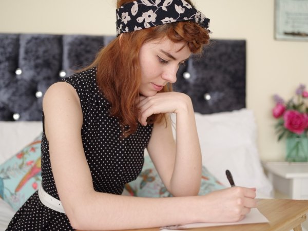 Kelly writing. She is wearing a vintage dress and headscarf.