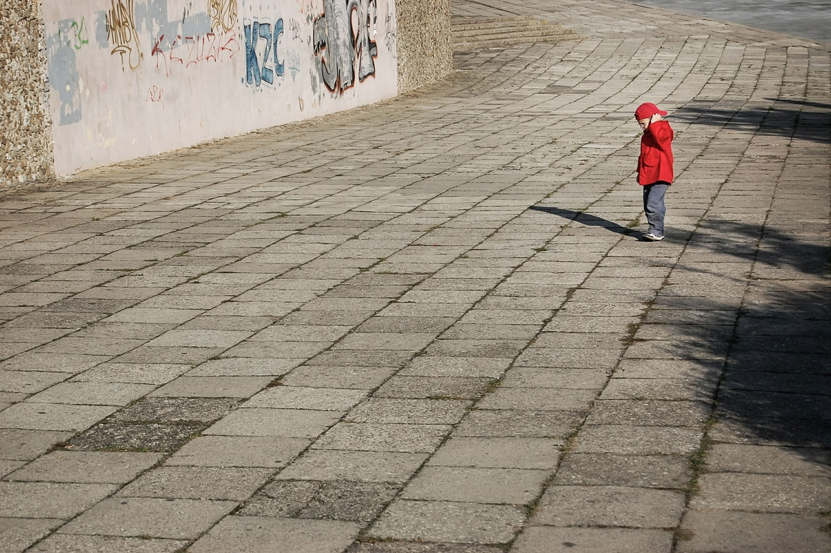 Young child in red coat standing on cobbled path