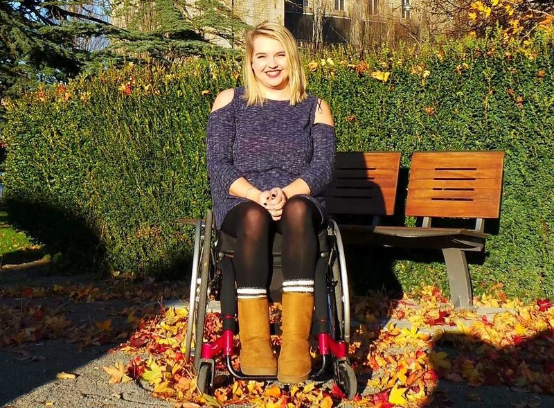 beth outdoors using wheelchair wearing dress and ugg boots and smiling at camera