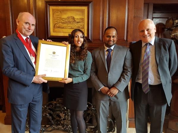 woman receiving an award from three men