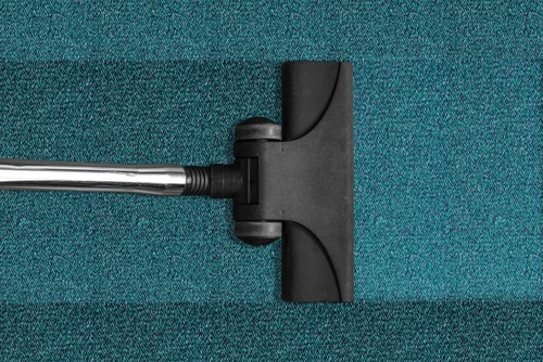 Head of a hoover moving across a blue floor