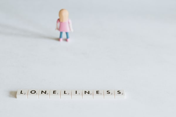 small toy figure standing alone in front of scrabble tiles that spell out the word loneliness