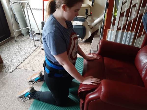 Ami kneeling on the floor doing physio