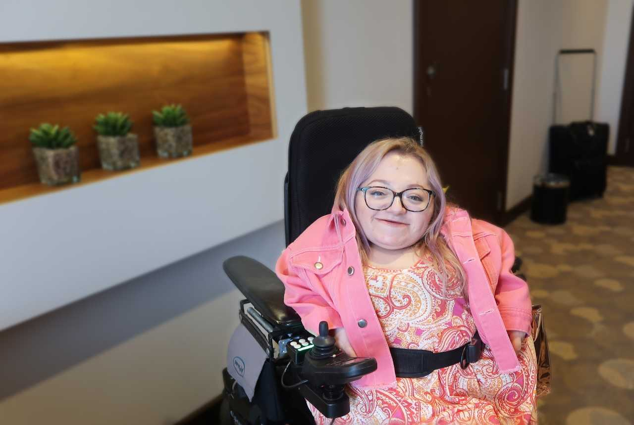 smiling young woman wearing glasses and a bright pink jacket in an electric wheelchair in a hotel room