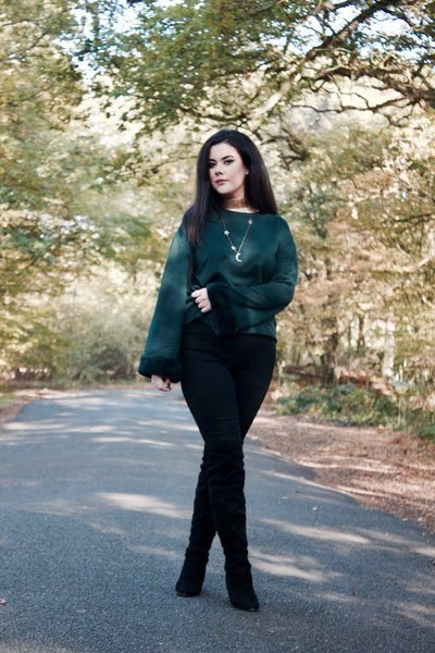 full length image of olivia wearing a dark green jumper star necklace jeans and boots with trees and woodland in the background