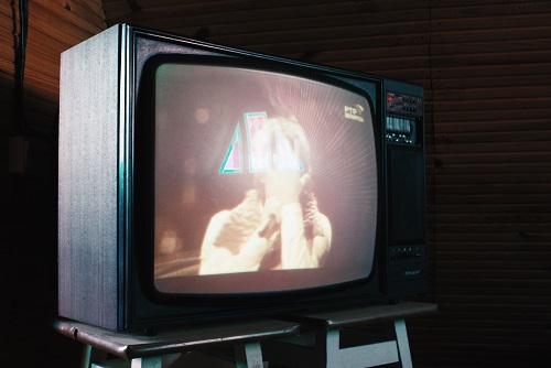 A retro style TV on a stand with a figure displayed
