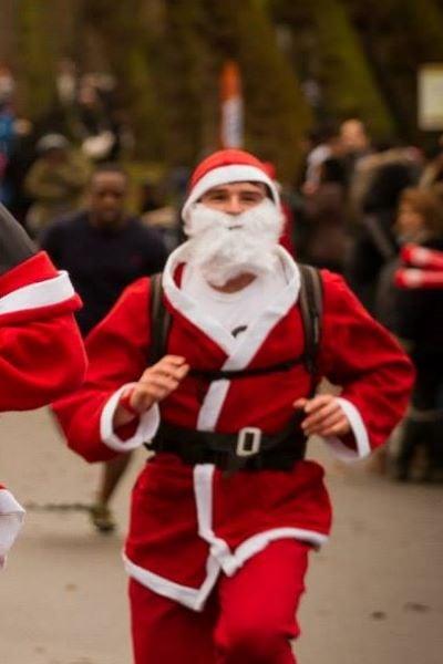 a man dressed in a santa costume running