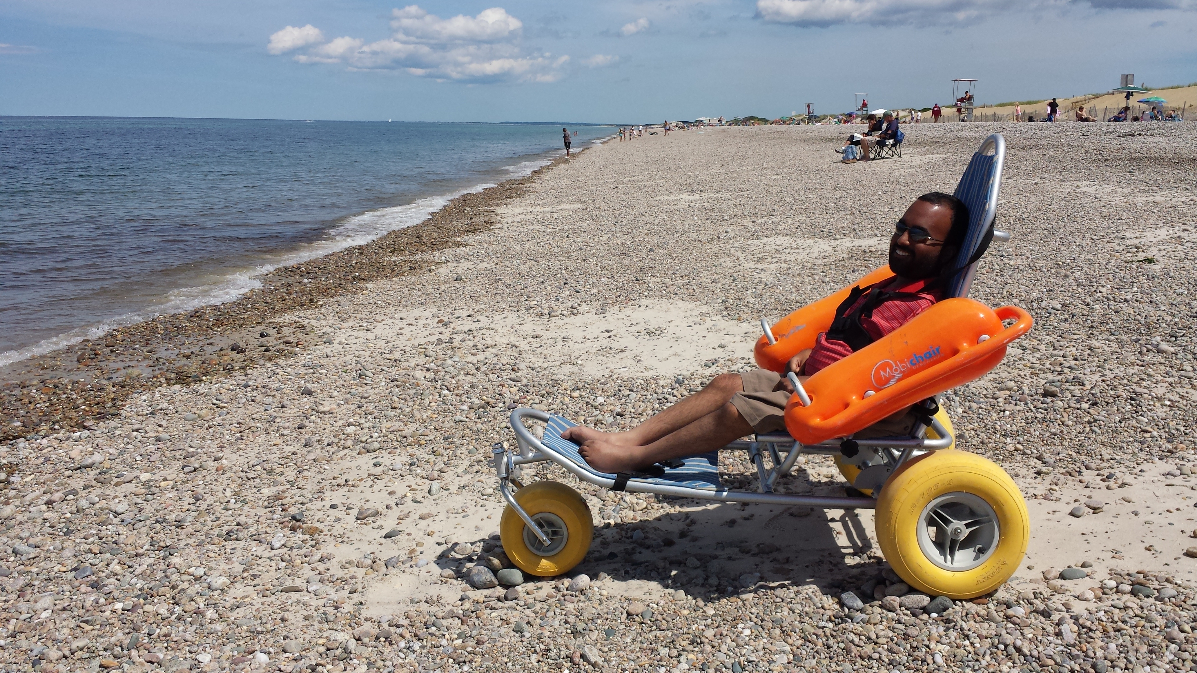 Man sitting on an adapted wheelchair on the beach next to the sea