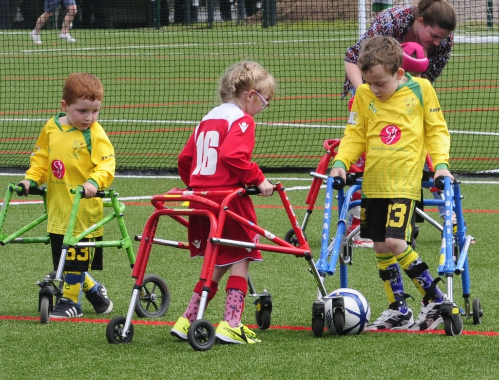 Children with walking frames playing football