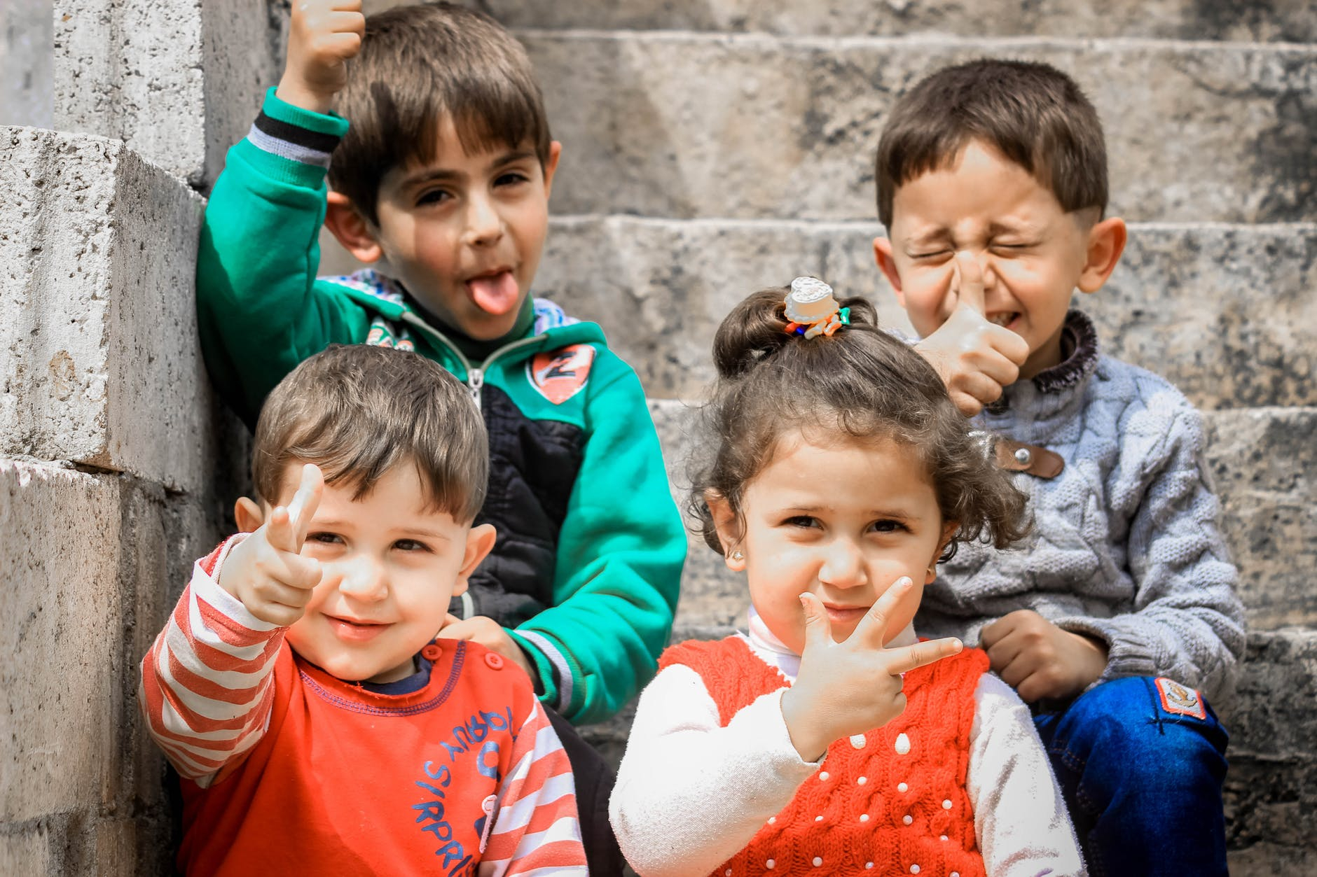 children making silly faces and showing a peace sign with fingers