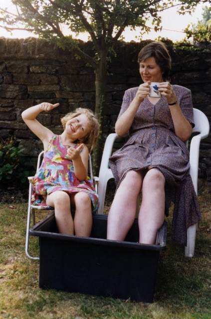 Photo of young girl and mother sitting in the garden, with their feet in a black box