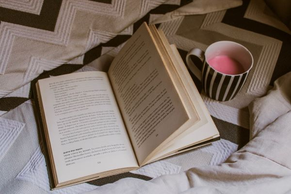 opened white book beside a white mug