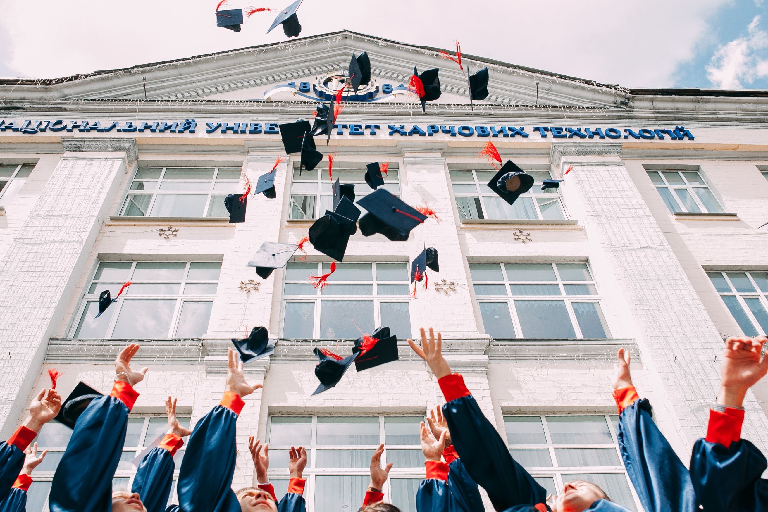 Picture of a crowd of students throwing their graduation caps up in the air outside a university