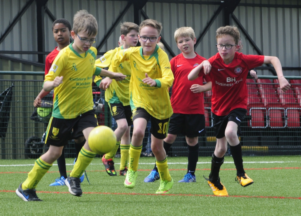 Group of young boys running after a football