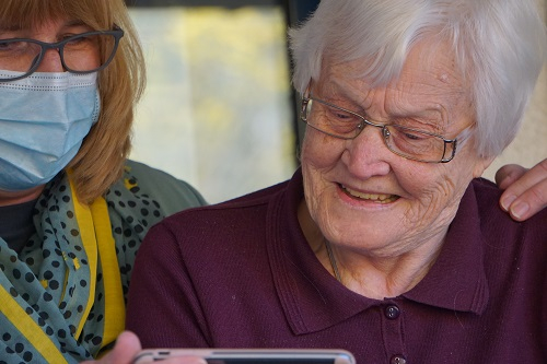 A man smiling at his phone accompanied by a carer wearing a face mask