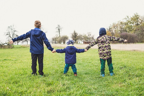 The backs of three children holding hands in a park