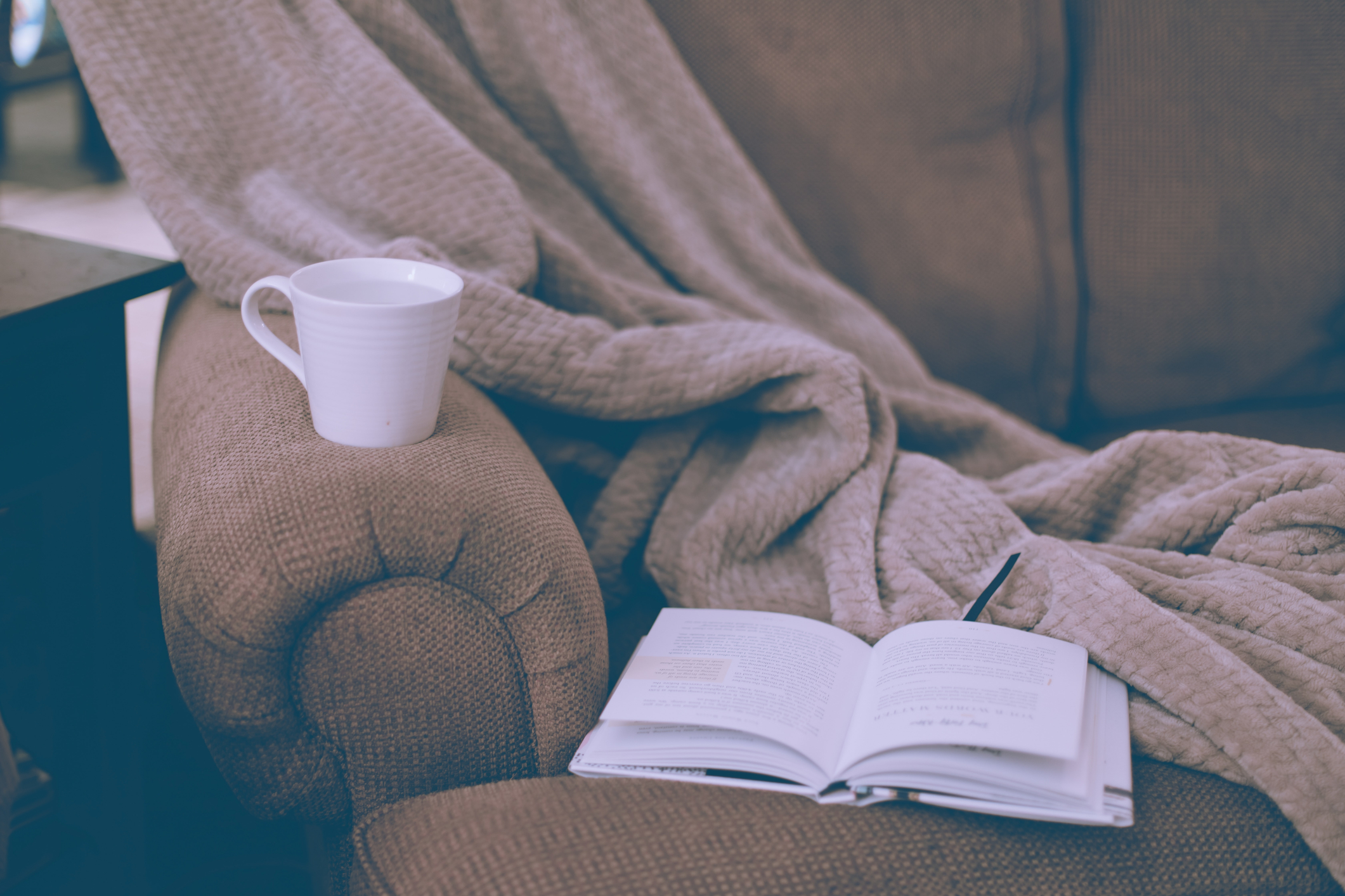 cosy image of a blanket book and mug on a sofa