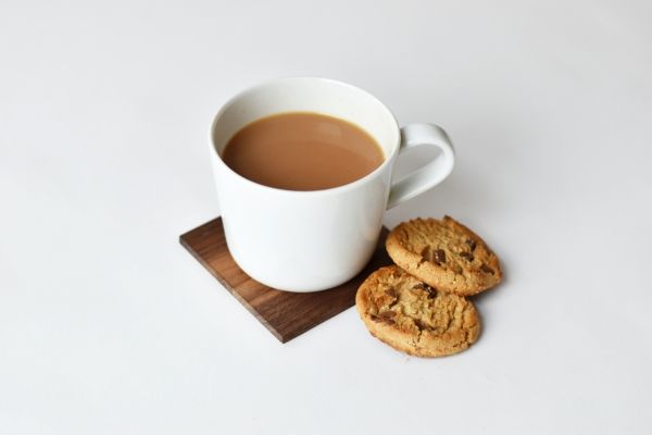 White background with a cup of tea in a mug and a cookie next to it