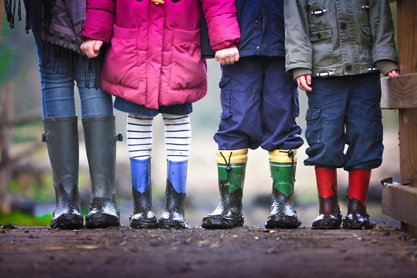 Children stood in a row wearing colourful clothing and wellington boots