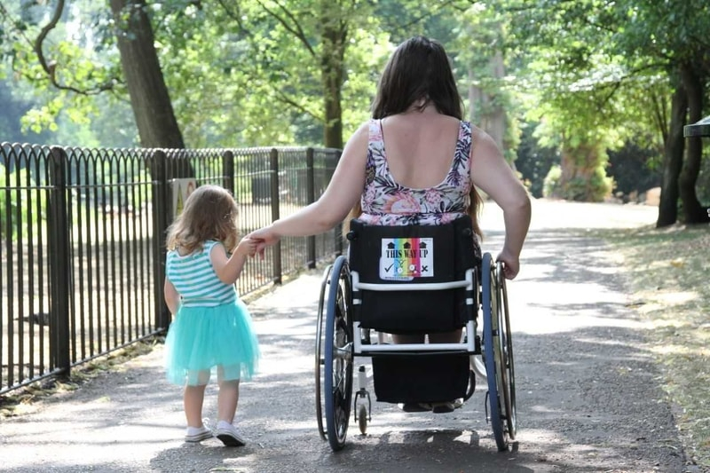 image taken from behind of danielle in her wheelchair holding hands with a toddler in a blue dress walking beside her