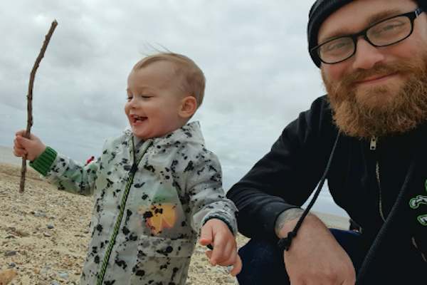 Joel and his son on a beach smiling with the sea in the background
