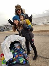 family by the beach with a toddler on one parents back