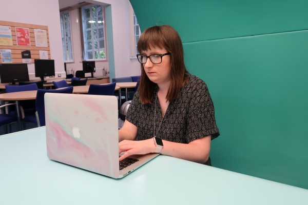 holly sat working at her desk looking at her laptop screen