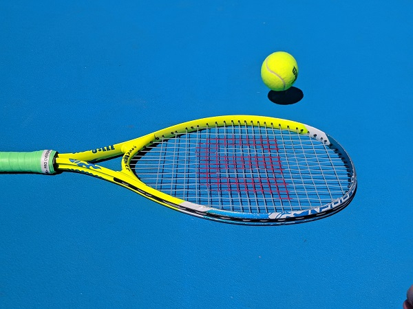 A tennis racket with a ball bouncing off it