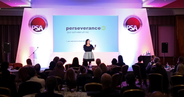 Liz on a stage that says perseverance at the back It is a central shot