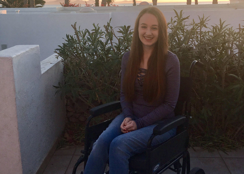 pippa outdoors sat in wheelchair smiling at camera