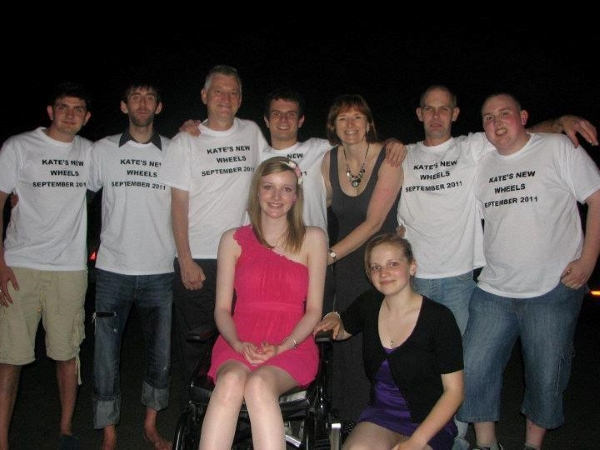 Kate in a wheelchair in the middle of the photo she a group of people on either side of her who are all wearing white t-shirts