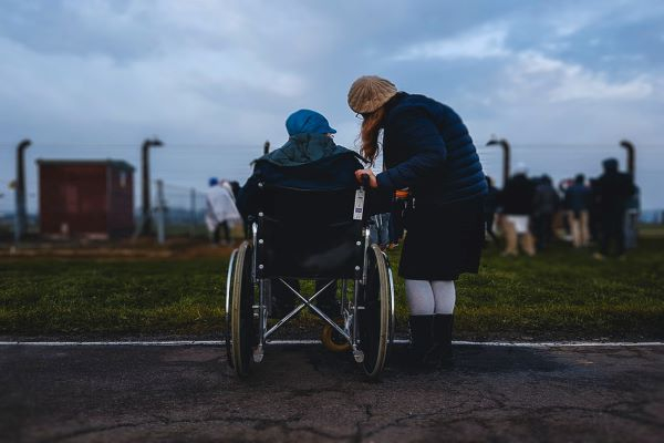 two people talking next to a green field one of them is a wheelchair user