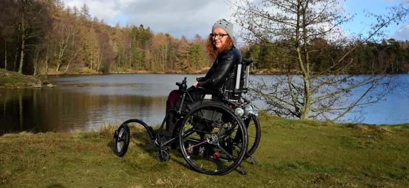 red haired woman in a sport wheelchair facing a lake and hills in the background and turning to smile at the camera