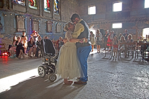 Man and woman doing their first dance in front of crowd, with woman standing in front of wheelchair
