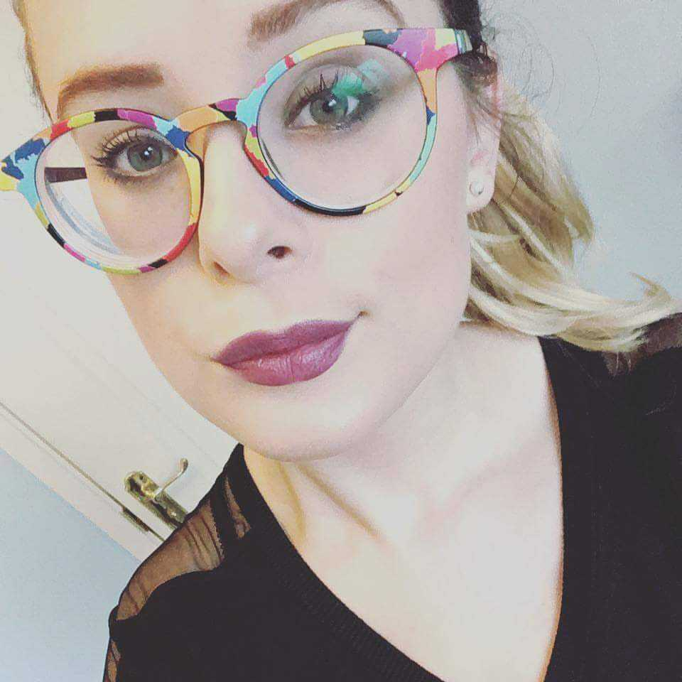 selfie of a blonde haired girl wearing a black top and multicoloured glasses