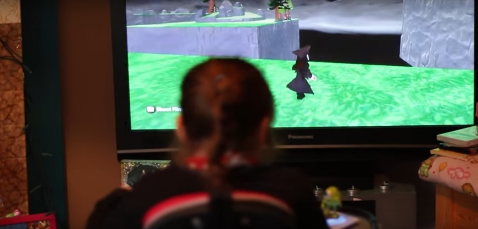 Young girl sat in front of TV screen playing video game