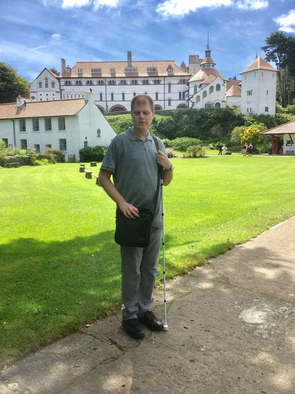 Man with sight impairment stood in gardens with white stick