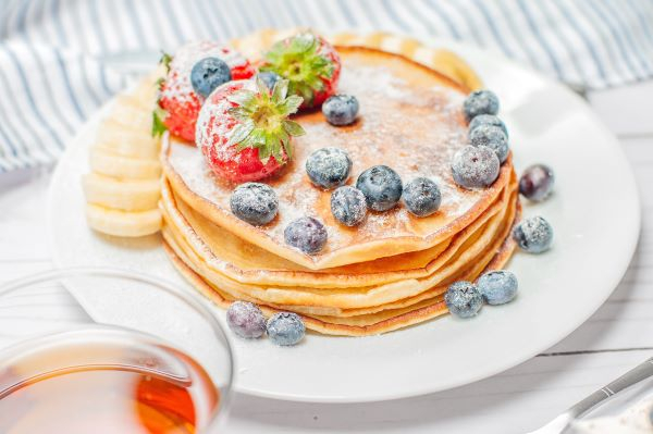 A stack of fluffy pancakes topped with blueberries and strawberries