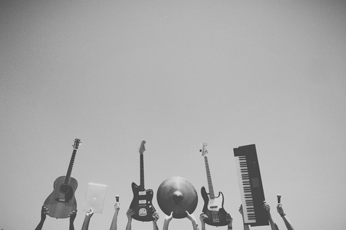 A row of hands holding up different instruments including - from left to right - a guitar laptop microphone electric guitar cymbal electric guitar keyboard and microphone