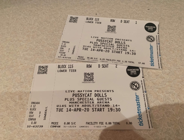 Two medium white paper concert tickets that have Pussycat Dolls at Manchester Arena written in bold black writing on them on a white background