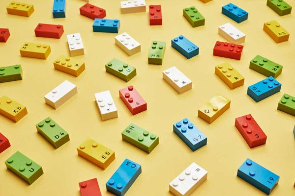 LEGO braille bricks scattered on a yellow surface Photo from LEGO dot com