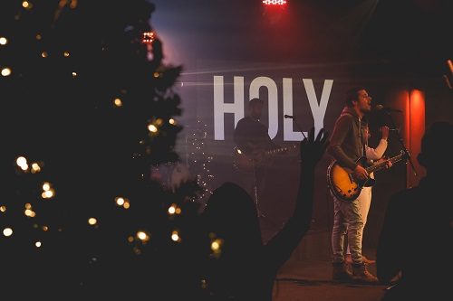 Guitarist on stage singing with a Christmas tree lit up in the foreground and the word HOLY behind them in big letters