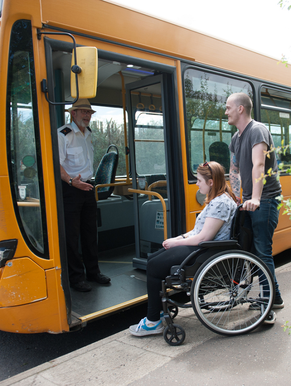 A young woman in a wheelchair waiting with a young man talking to a bus driver who is aboard a yellow single-decker bus