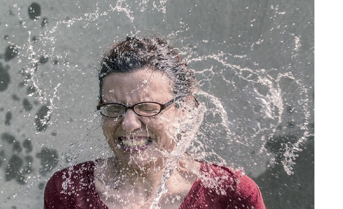 Lady being splashed in the face with cold water