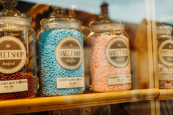 A row of glass jars that are full f different types of sweets